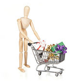 Wooden character with shopping cart and Christmas gifts — Stock Photo