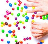 Women's hands gathering candies — Stockfoto