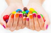 Vrouw handen bedrijf snoepjes met heldere manicure — Stockfoto
