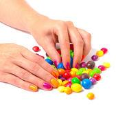 Ręce kobiety z jasnymi manicure, zbierając kolorowych cukierków — Zdjęcie stockowe