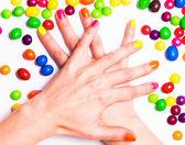 Młoda kobieta ręce skrzyżowane z jasnym manicure i cukierki wokół — Zdjęcie stockowe