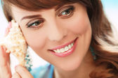 Smiling and looking away woman with a seashell — Stock Photo