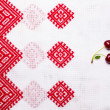 Sweet ripe cherry on bright white Ukrainian tablecloth with red — Stock Photo #51522811