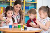 Roztomilé děti kreslení s učitelem na předškolní třída