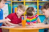 Roztomilé děti kreslení s barevnými nátěry ve školce