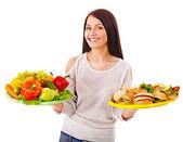 Woman choosing between fruit and hamburger.