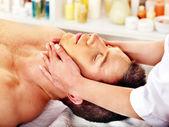 Muž dostává masáž obličeje