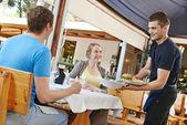 Pincér kínáló étteremben a fiatalok