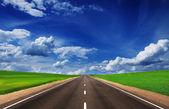Aszfalt road, zöld mezők, gyönyörű ég alatt