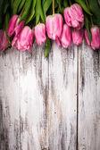 Růžové tulipány dřevěný stůl
