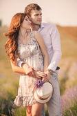 Fiatal pár-kültéri szerelmes. Lenyűgöző szabadtéri portréja érzéki fiatal divat pár pózol nyáron mező
