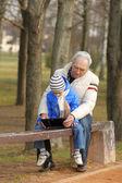 Großvater und Enkel suchen Tablet auf Bank im freien
