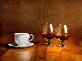 Zwei Kelche von Brandy und Tasse heißen Coffeeon hölzernen alten Zähler
