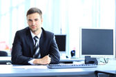 Mladý podnikatel pracují v kanceláři, sedící u stolu