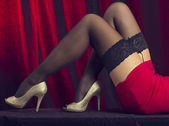 Womans stockinged legs over cabaret red background