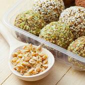 Cibo sano macrobiotico. palle da terra germogli di grano con sesamo e verde granelli di semi di zucca in scatola di plastica. chicchi germinati in cucchiaio di legno