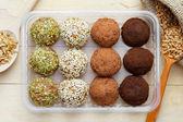 Macrobiotica alimentazione sana: palle da terra germogli di grano con sesamo, semi di zucca e granelli di cioccolato in scatola di plastica. chicchi germinati in cucchiaio di legno sul tavolo, vista dallalto
