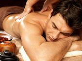 Muž s masáž zad ve spa salonu