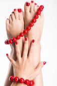 Closeup fotografie ženských nohou s krásným červeným pedikúra