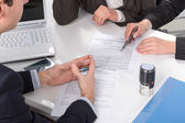 Ruce tří lidí, podepisování dokumentů