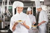 Happy Chef Presenting Dish In Industrial Kitchen