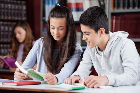 Teenage Friends Studying Together At Desk