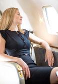 Bohatá žena dívá oknem soukromé letadlo