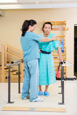 Fisioterapista, assistere il paziente maschio in piedi