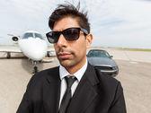 Jistý podnikatel před auto a soukromé letadlo