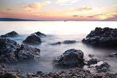 Sunrise on rocky sea coast and blurred water