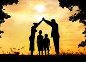 Silueta, skupina šťastných dětí hraje na louce, západ slunce, s