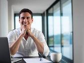 Obchodní muž pracuje na přenosném počítači doma