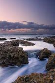 Sunrise landscape of ocean with waves clouds and rocks