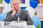 Senior uomini seduti davanti di compleanno torta chiedono quanti anni sono io
