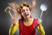 Pazza casalinga con i bigodini in testa e martello