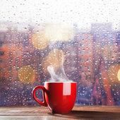 Tazza di caffè fumante sopra un fondo di paesaggio urbano