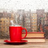 Kouřící šálek kávy na deštivý den okno pozadí