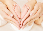Neugeborenes Baby Füße in Händen der Eltern. Liebe Simbol als Herzschild
