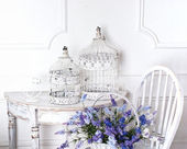 Vintage Stuhl und Tisch mit Blumen im Vordergrund und Käfige