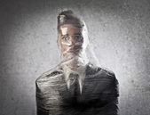 Un uomo daffari è intrappolato nella plastica