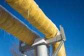 Bílé průmyslové potrubí studené a teplé vody se žlutým tepelnou izolací