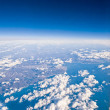Постер, плакат: Clouds top view from the window of an airplane flying in the cl