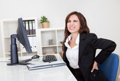 Giovane imprenditrice avendo dolore alla schiena mentre seduto alla scrivania ufficio