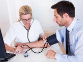 Attraente giovane donna medico o infermiere prendendo un maschio pazienti utilizzando un misuratore di pressione del sangue