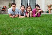 Boldog fiatal család feküdt a füvön portréja