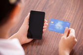 Üzletasszony fizetéskor a mobiltelefon