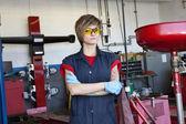 Portrét mladé ženy mechanik nosit ochranné vybavení s náručí přešel v dílně