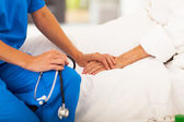 Lékař se drží za ruce senior pacienta a uklidňující ji