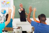 Studenty středních škol s rukama vzhůru v učebně