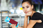 Pretty businesswoman with air ticket at airport